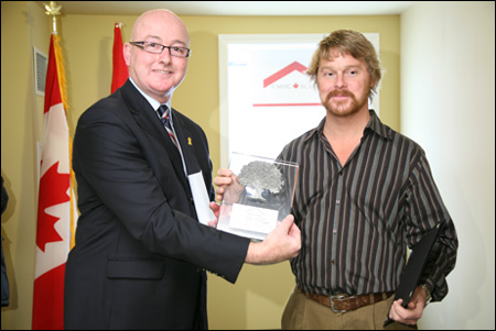 Mr. David Sweet, Member of Parliament for Ancaster-Dundas-Flamborough-Westdale, presents a commemorative plaque to Chris McNabb, President, King Street Holdings Limited. The Cordage Lofts provides 28 new affordable rental apartments for low-income individuals.